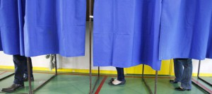 938978_the-legs-of-voters-are-seen-behind-blue-curtains-in-voting-booths-in-a-polling-station-during-the-first-round-of-the-2012-french-presidential-election-in-vaulx-en-velin
